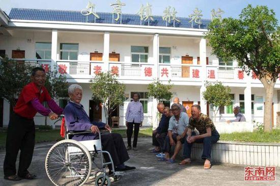 曹贵生推着周兴海来到院子里,帮助老人加强身体锻炼。