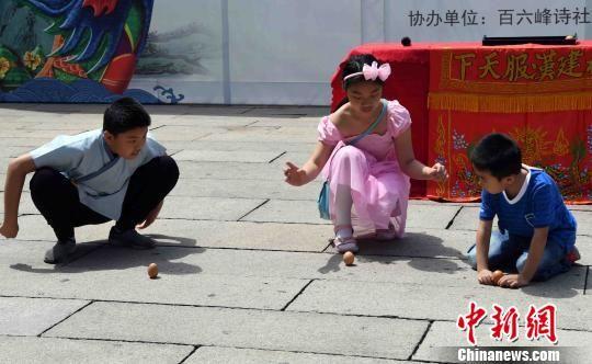 """三名孩童体验传统端午民俗""""立蛋""""。 刘可耕 摄"""