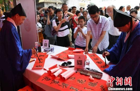 """福州百六峰诗社的老先生们教市民书写""""午时书"""",红纸上的毛笔字表达着人们最诚挚的端午祝福。 刘可耕 摄"""