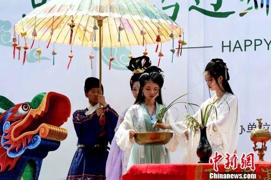 """福建汉服天下协会志愿者按照古时候端午习俗,为现场观众""""沐兰汤""""。 刘可耕 摄"""