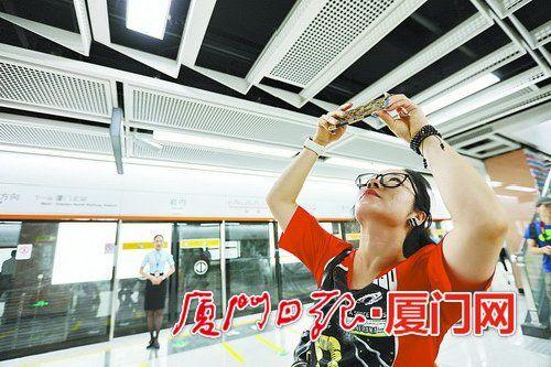 市民拿起手机拍下车站的各种装饰细节