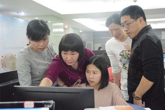 庄丽云(左二)与工作团队研讨业务