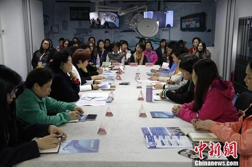 10月12日,正在北京参加第九期澳门妇女工作骨干研习班的20多位成员与北京妇联和有关社会组织负责人进行座谈,就妇女组织参与社会管理的经验与做法进行交流。中新社记者 夏守智 摄