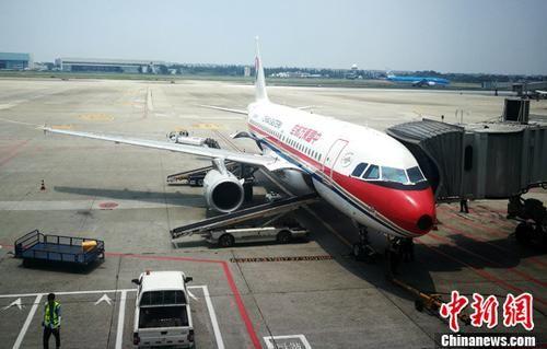 资料图:停机坪上正在上客的客机。 中新社记者 刘忠俊 摄