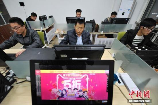 """资料图:电商公司员工奋战""""双十一""""。 中新社记者 韦亮 摄"""