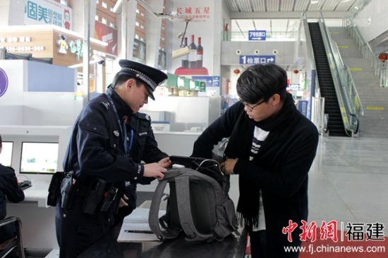 执勤民警正在对行李物品进行开包检查。