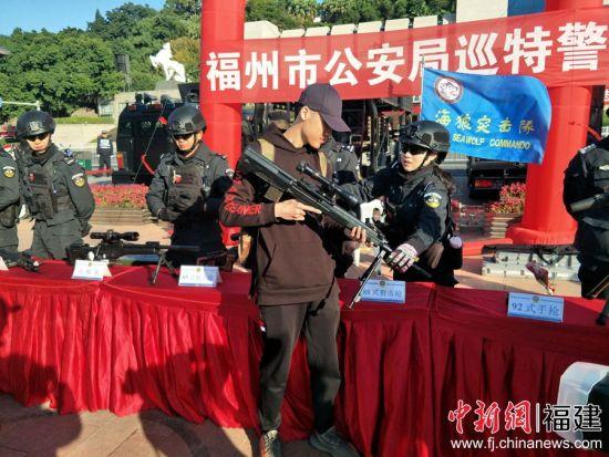图为市民在特警的帮助下了解警用装备。林玲 摄