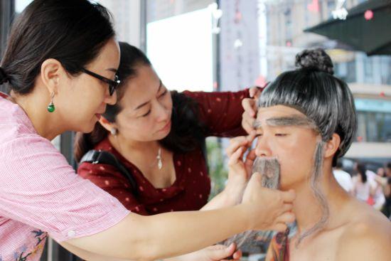 詹红丹(中)为演员化妆。