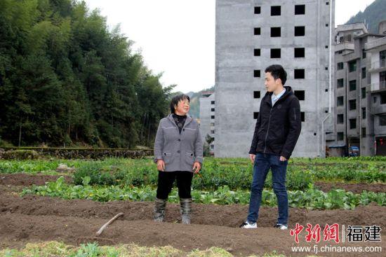 图为扶贫干部询问蔬菜种植情况。吴苏梅 摄