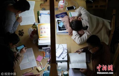 资料图:2017年12月7日,郑州大学新校区,考研进入倒计时。图为夜晚的图书馆里,考研学生占了相当大比例。马健 摄 图片来源:视觉中国