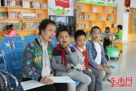 鼓楼区一所小学的学生们放学后等待家长来接时,听退休教师讲故事。本网记者 张立庆 摄