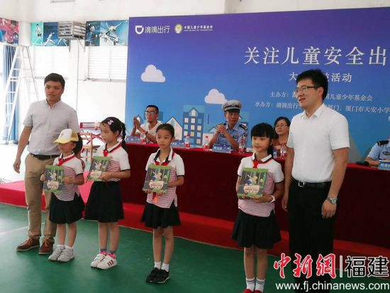 向小朋友赠送儿童安全出行绘本。