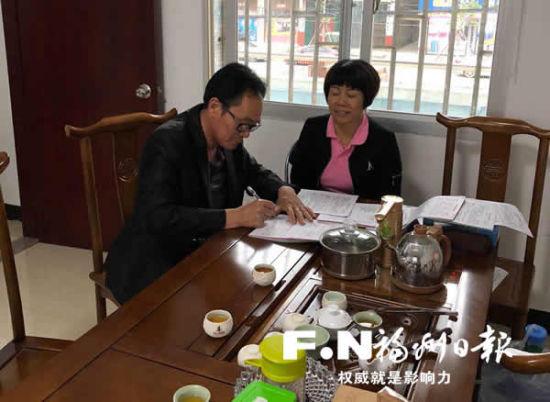 方秀容(右)与群众耐心解释政策后,群众在征迁协议上签字。