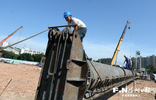 工人在奥体颐养中心建设工地安装桩机。