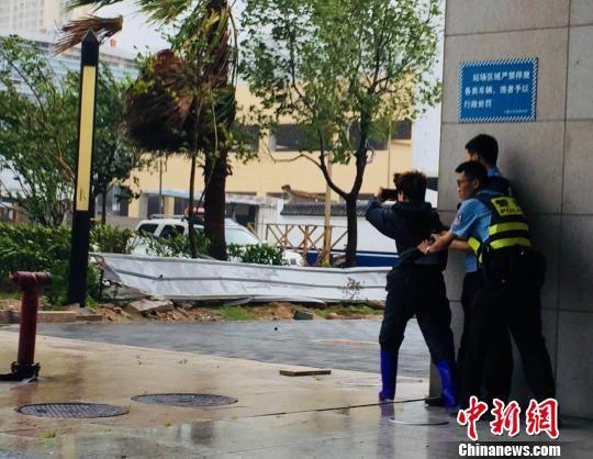 图为记者(左)在现场拍摄台风经过情况。 林冬冬 摄