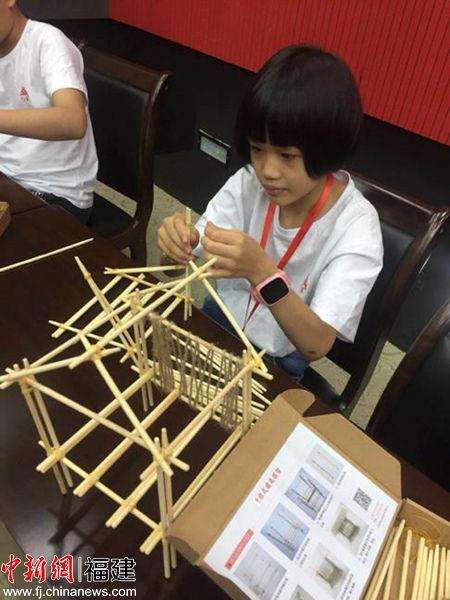 同学们认真搭建干栏式建筑模型