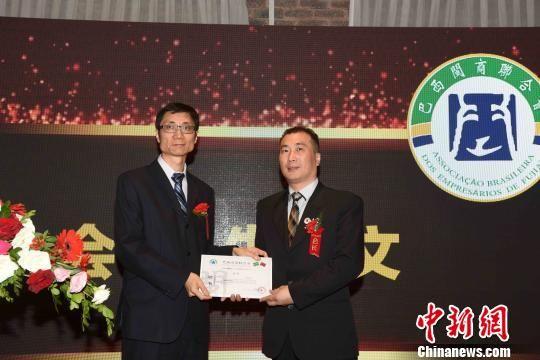 图为中国驻圣保罗副总领事孙仁安(左)为巴西闽商联合会新任会长朱明文颁发任职证书。 莫成雄 摄