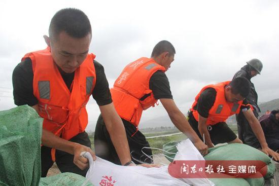 武警官兵在用沙袋加固海堤