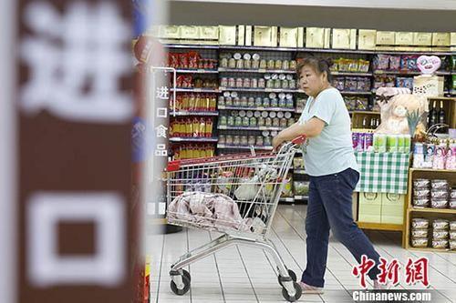 资料图为某超市,一女子正在挑选商品。中新社记者 张云 摄