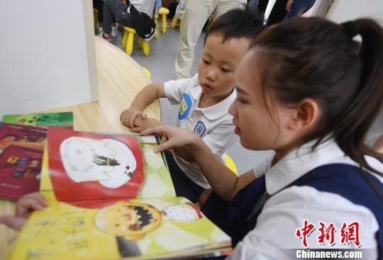 澳门真人博彩娱乐官网市鼓楼区温泉街道传初幼儿园一名老师正陪伴小朋友阅读图画书。 记者刘可耕 摄