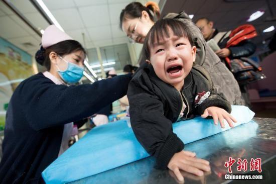 资料图:家长带着孩子前来挂号看病。 武俊杰 摄