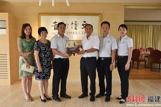 湄洲妈祖祖庙董事会董事长林金赞(左三)与菲律宾著名侨领陈祖昌先生(右三)互赠纪念品。