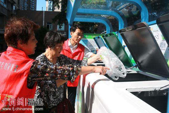 宣导员张永琼在分类亭前井井有条地指导居民进行垃圾分类。陈丽霞摄