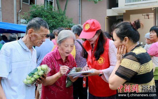 """工作人员正在为居民讲解""""垃圾分类志愿书""""。陈丽霞摄"""