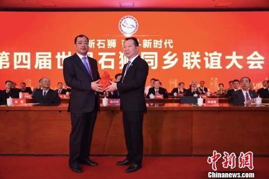 林嘉南(右)当选世界石狮同乡联谊会第四届理事会理事长。图为会长印信交接仪式。 陈龙山 摄