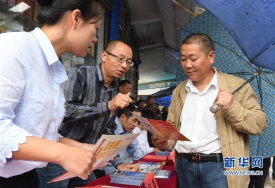 10月10日,福鼎市纪检监察干部在管阳镇西阳村集市向村民先容信访告发流程。
