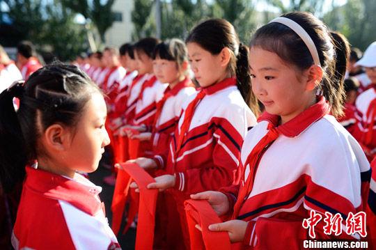 资料图:某小学高年级同学为一年级新生佩戴红领巾。(图文无关) 中新社记者 刘文华 摄