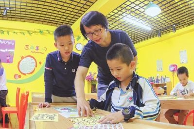 悦港社区党员韩雪琴在教小朋友画画。