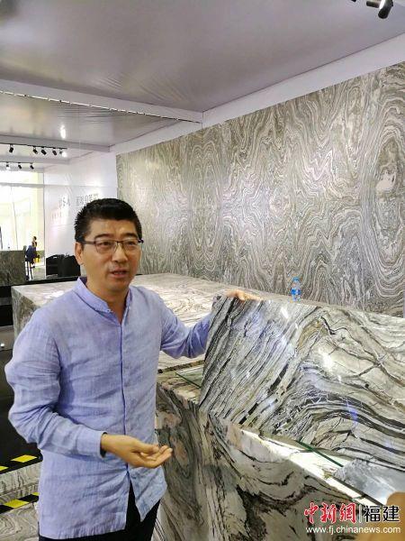 英良集团董事长刘良向记者展示一款薄、软、可弯曲适用于汽车内饰的石材产品。
