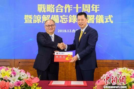 厦门银行董事长吴世群(右)代表厦门银行向富邦金控总经理韩蔚廷发放股权证。 供图 摄