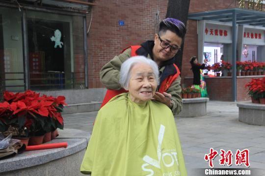 志愿者为老人义务理发。 彭莉芳 摄