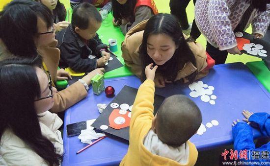 """4.协和学院志愿者与自闭症儿童互""""喂""""汤圆。陈可铭 摄"""