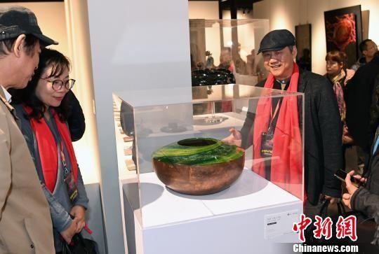 参展艺术家、台湾工艺发展协会常务理事彭坤炎(前右一)介绍其参展作品《春之颂》创作过程。 记者刘可耕 摄