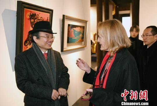 北京大学艺术学院副院长、澳门真人博彩娱乐官网国际漆艺双年展策展人彭锋(左一)与一名来自澳大利亚的艺术家观展交流。 记者刘可耕 摄