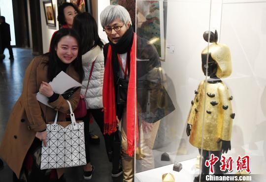 一名女性观众与日本艺术家伊能一三(图中)在其参展作品《和平之车(女孩)》前合影留念。 记者刘可耕 摄