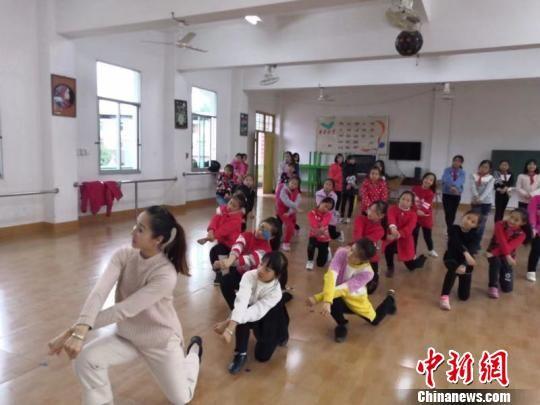 图为50号志愿者洪巧明带领三明市清流县长校中心小学孩子们跳舞。 吕明 摄