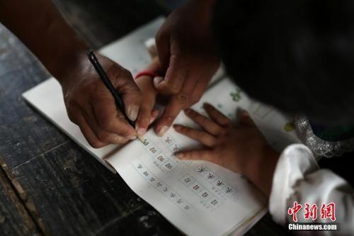 老师辅导一年级学生写作业 图文无关 中新社发 黄晓海 摄