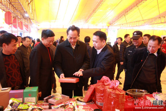 与会领导嘉宾参观现场展出的当地美食名产。(王伟鹏 摄)