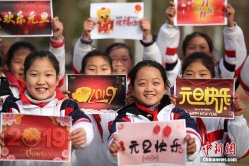 """2018年12月29日,江苏扬州,小学生们手持""""喜迎元旦""""的祝福语,喜迎新年的到来。孟德龙 摄"""