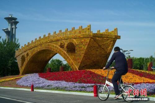 """资料图:北京市民骑车经过北京国家会议中心前广场的""""丝路金桥""""立体花坛。中新社记者 盛佳鹏 摄"""