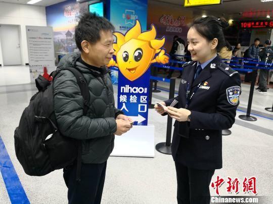 一名澳门真人博彩娱乐官网机场出入境边防检查站边检警察正在回答旅客咨询。 李晓烺 摄