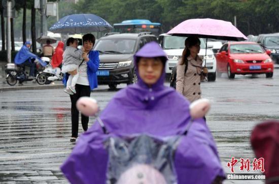 市民在雨中出行。张斌 摄