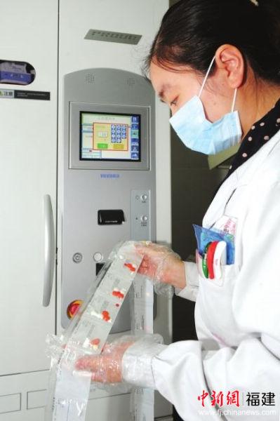 """机器人""""药师""""将病人药品逐一包装后送出。闽东医院供图"""