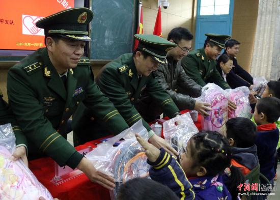 支队官兵为贫苦门生赠予进修用品。武警南平支队供图