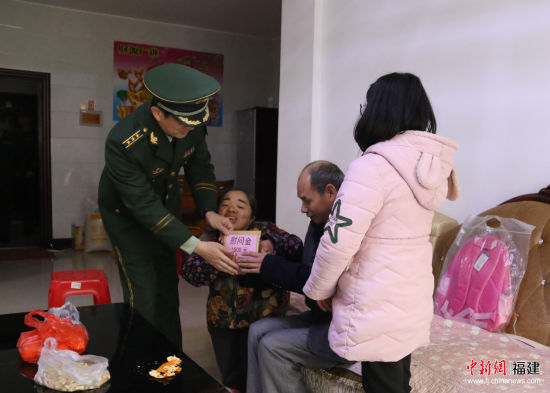 张晓刚代表支队官兵为周有鑫一家送上慰问金。武警南平支队供图