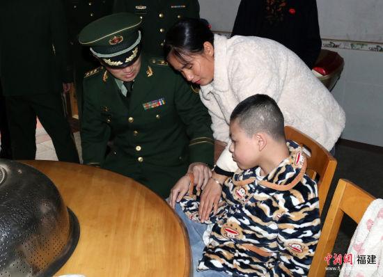 张晓刚询问陈毅博的病情。武警南平支队供图